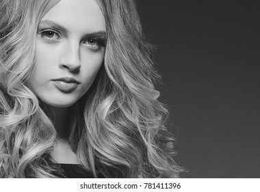 Woman beauty healthy skin and hairstyle, brunette with long hair over dark background female portrait. Studio shot.Black and white