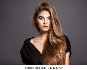 Woman with beauty long brown hair.  Beautiful face of an attractive  model with blue eyes. Closeup portrait of a caucasian female. Attractive fashion model.