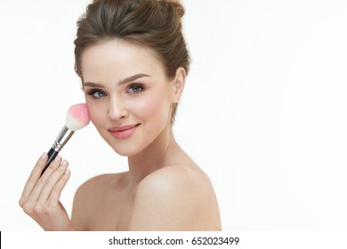 Woman Beauty Makeup. Closeup Of Young Woman With Brush In Hand Putting Loose Blush On Facial Skin. Portrait Of Sexy Female Model With Natural Makeup On White Background. Cosmetics. High Resolution