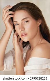 Frau. Schönes Porträt von jungen Models TouchGesicht. Schöne Brunette mit natürlichem Make-up und perfekter Haut.