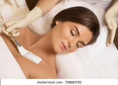 Woman in beauty salon with moistering mask applied on decollete zone