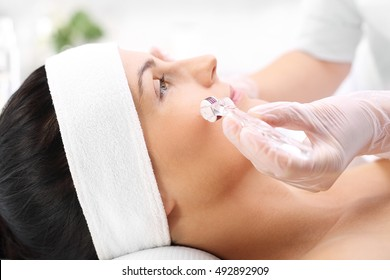 The woman in the beauty salon for the treatment mezotrrapii with the use of micro needle roller.
