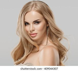 Woman beauty skin care close up portrait blonde hair studio on gray