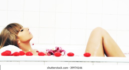 woman beauty spa and wellness treathment with red flower petals in bath