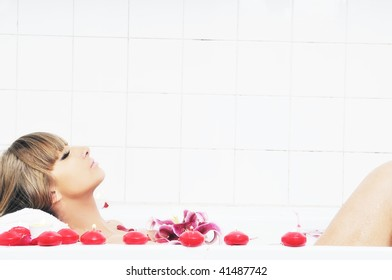 woman beauty spa and wellness treatment with red flower petals in bath with milk
