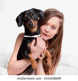 Woman in bed holding her dog.