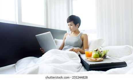 Woman in bed with laptop and breakfast