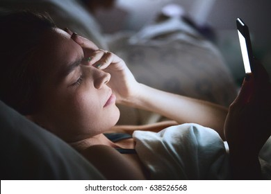 Woman in bed with phone, headache