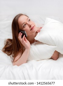Woman in bed talking on phone.