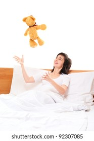 Woman in bed throwing teddy bear isolated on white