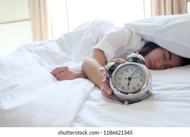 Woman in bed trying to wake up with alarm clock.