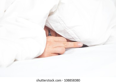 woman in bed under blanket shows the middle finger