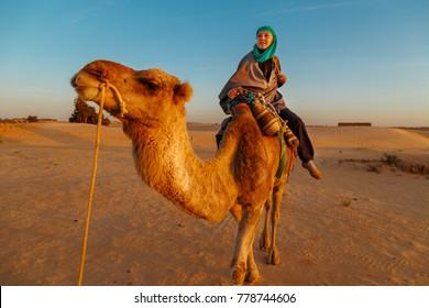 Woman in Bedouin clothes riding a camel in the Sahara desert, Tunisia, Africa.