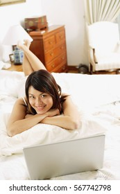 Woman in bedroom, lying on bed, laptop open in front of her
