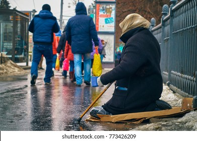 Woman beggar with walking stick asking for money on Moscow street in winter