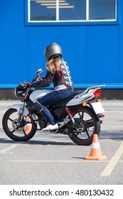Woman beginner doing exercise around cones on the motorbike in skill training motordrome. Russian driver school