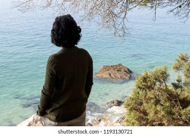 woman from behind by the sea