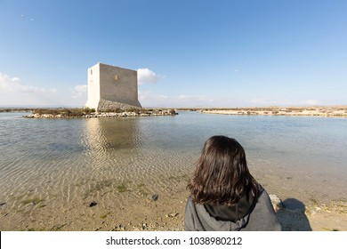 Woman from behind contemplating the landscape of the Natural Park of Las Salinas in Santa Pola, province of Alicante, Spain.