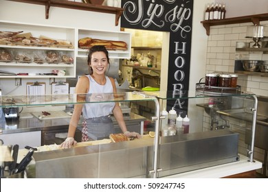 Woman behind the counter of sandwich bar looking to camera