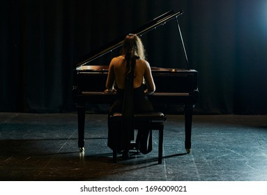 A woman from behind dressed in a black dress playing a black grand piano with the lid raised on a stage
