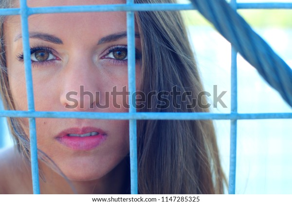 woman behind fence metal cage jail issue