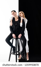 Woman behind. Handsome model sitting on chair and appealing blonde-haired woman standing behind him