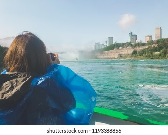 Woman from behind photographing and observing from a boat that makes excursions, with blue plastic raincoat, the Niagara Falls in Canada and America.