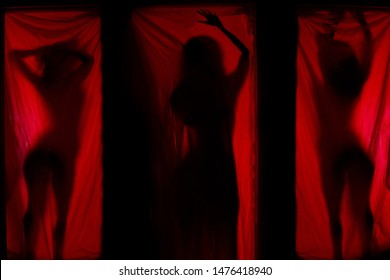 Woman behind red curtains. Prostitute or stripper