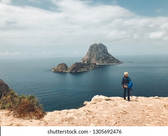 Woman from behind, watching the islets of Es Vedrá, from the cliff of the natural park of Cala D'hort, in Ibiza, Spain