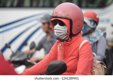 A woman behind the wheel of a motor scooter in a hood and a protective helmet with a mask and sunglasses in a city street. Vietnam.