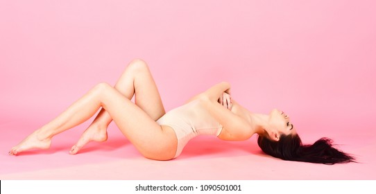 Woman in beige bustier lay, pink background. Lady in bodysuit, slim, young and healthy. Girl with smooth skin enjoying after care procedure, depilation, wellness and spa. Wellness and spa concept