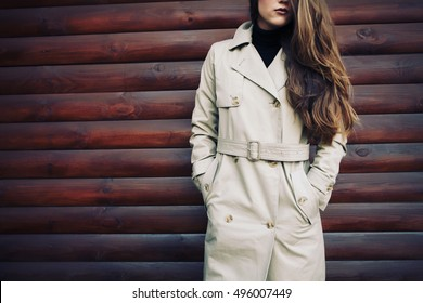Woman in beige coat outdoors closeup. Autumn fashion trend, details toned style instagram filters