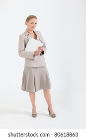 Woman in a beige skirt suit with a folder