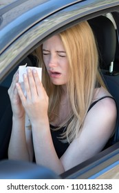 Woman being allergic and having hay fever in car