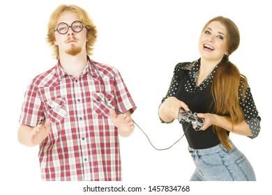 Woman being bossy having fun while steering man using gaming pad. Female controling her boyfriend.