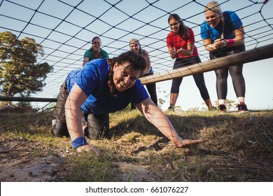 Woman being cheered bye her teammates during obstacle course training in the boot camp