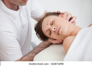 Woman being massaging by the doctor while having the head turn in the side indoor