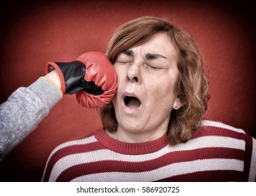 Woman being punched with red boxing glove in her face. Computer added  dust, scratches, grain and vignette