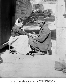 Woman being tattooed by a man in a fez,'Tattoing a pilgrim', Jerusalem, American Colony Photo Department, 1900-1920.