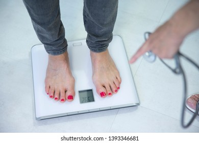 Woman being weighed at the doctor's.