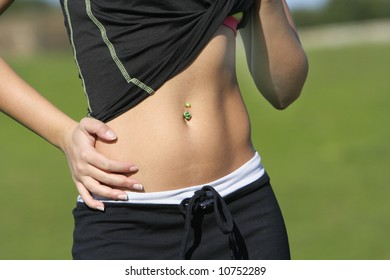 woman belly with a green pircing