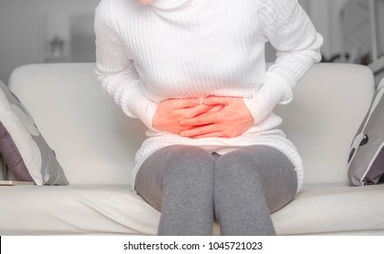 woman with belly pain or  stomachache.Acute Inflammation in a woman intestine. Female holding hand to spot of belly-aches . Concept photo with read spot indicating location of the pain.