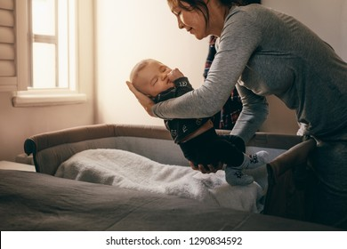 Woman bending forward to put her infant kid in a bedside bassinet. Mother holding her sleeping baby to lay him on his bed.