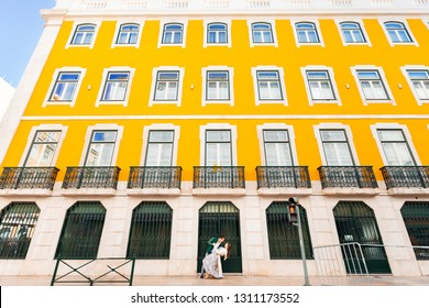 woman bent back and the man hold her waist near the building with yellow walls in Lisbon