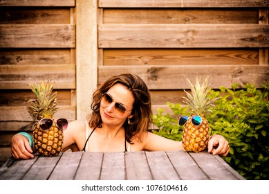 woman between two pineapples wearing sunglasses, as if she's between her best friends