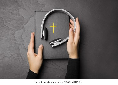 Woman with Bible and headphones at black table, top view. Religious audiobook
