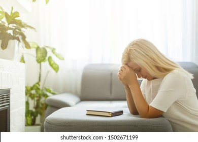 Woman with bible praying home