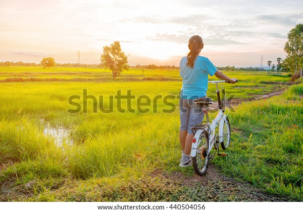 Woman with bicycle countryside in summer. Foldable Bike.