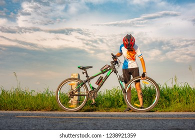 woman bicycle cyclist in trouble of front tire wheel needs repair and adjusting by herself on the road
