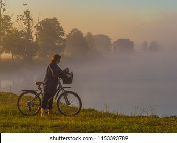 A woman with bicycle  during the foggy morning. Bug River.  Podlasie. Podlachia. Poland, Europe. The region is called Podlasko or Podlasze. Panoramic view.